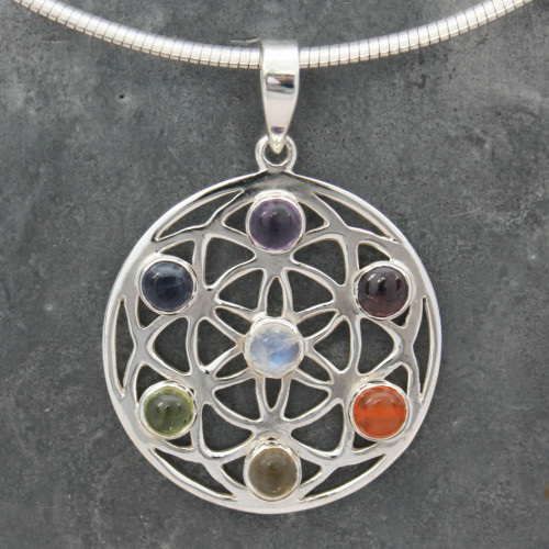 sterling silver Chakra Flower, Seed of Life Pendant contains a corresponding stone for each of the seven Chakras, starting at the Crown with Rainbow Moonstone (centre of the Seed of Life) followed by: Amethyst, Iolite, Peridot, Citrine, Carnelian and Garnet at the Root Chakra.